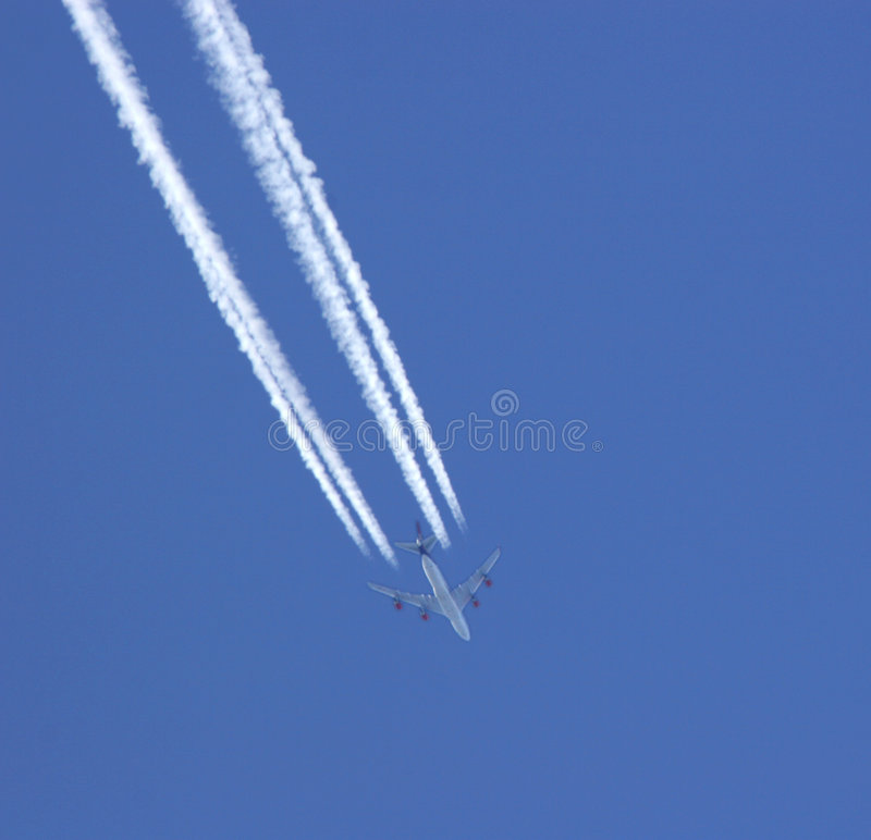 Flying High. Jet aircraft flying at high altitude with jet trails, set against a blue sky stock image