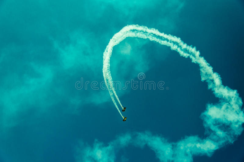 Flying High as a team. Two air-crafts team up to show stunts and loop in the sky royalty free stock images