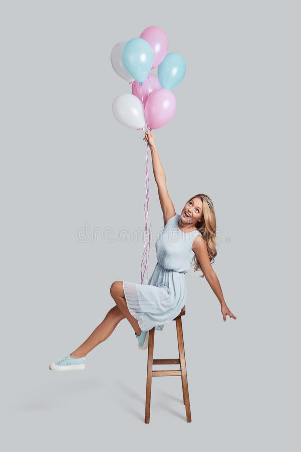 Flying high... Full length studio shot of attractive young woman in crown holding balloons while hovering in air against grey background royalty free stock images