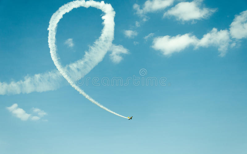 Flying High. A vintage craft leaves trail as it loops and flies ahead stock photo