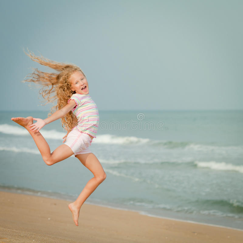 Flying jumping beach girl at blue sea shore stock images