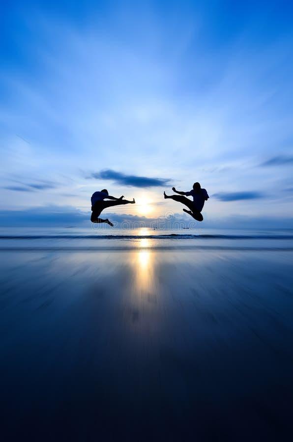 Flying kick VS flying kick. Near the beach when sun rising stock photography