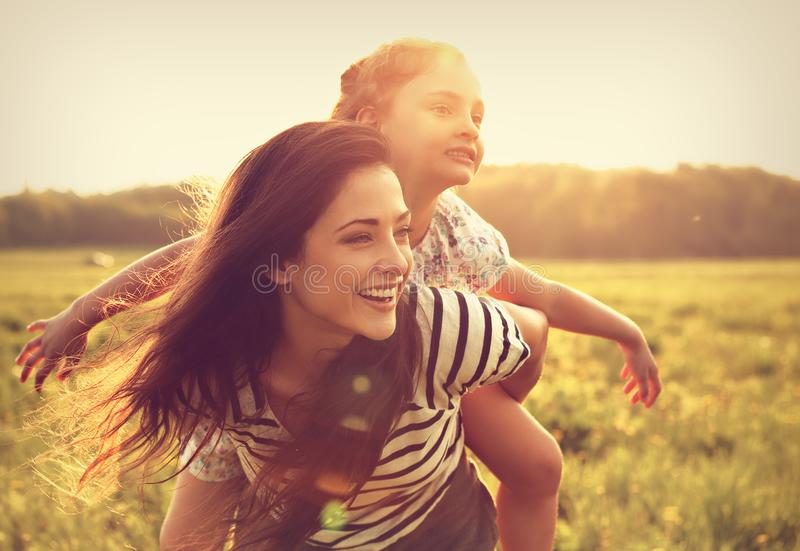 Flying kid girl laughing on the happy enjoying mother back on sunset bright summer background. Closeup portrait. stock photo