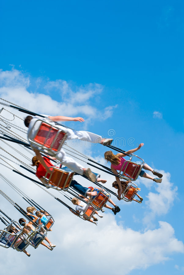 Flying kids on carousel. Happy kids on swinging carousel at blue cloudy sky royalty free stock photography