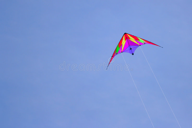 Flying kite. Against a deep blue sky royalty free stock image
