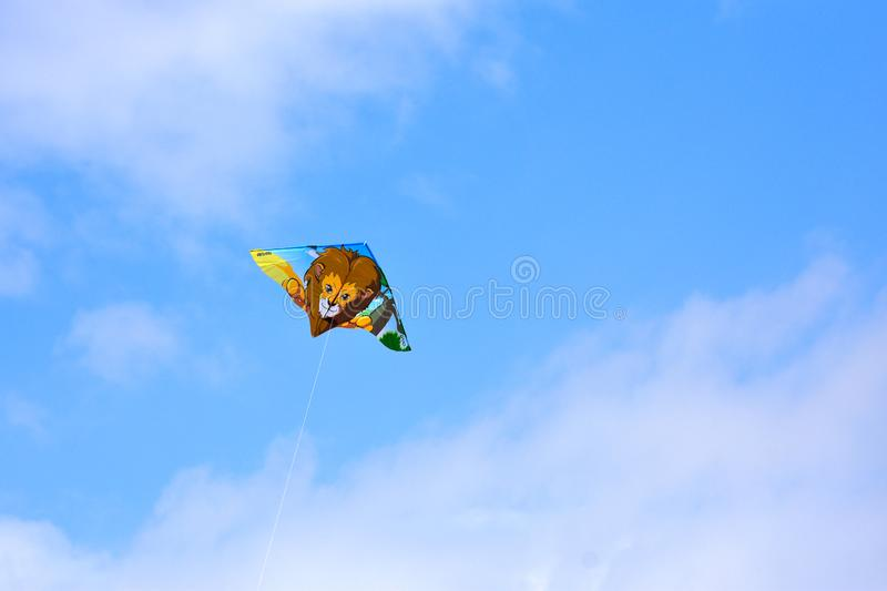 Flying a kite in a blue and cloudy sky stock photos