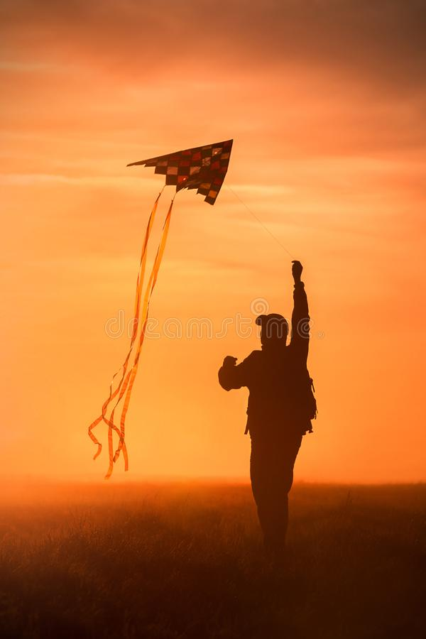 Flying a kite. Silhouette of a man with a kite against the sky. Bright sunset royalty free stock images