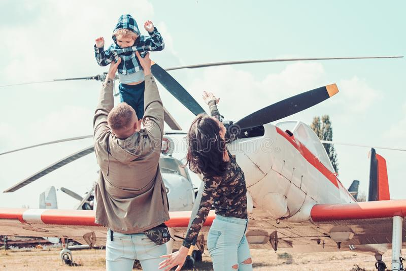 Flying like a bird. Woman and man with boy child at helicopter. Happy family vacation. Family couple with son on stock photography