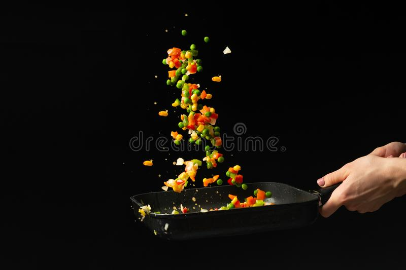 Flying mixed vegetables in a pan. Diet healthy food. Black background for copying text. Concept of food and cooking. stock photos