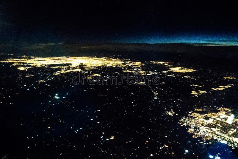 Flying at night over cities below royalty free stock photo