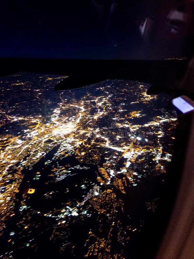 Flying at night over cities below stock photo