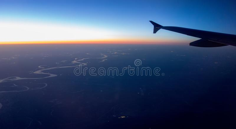 Flying at night over citiesbelow stock photography
