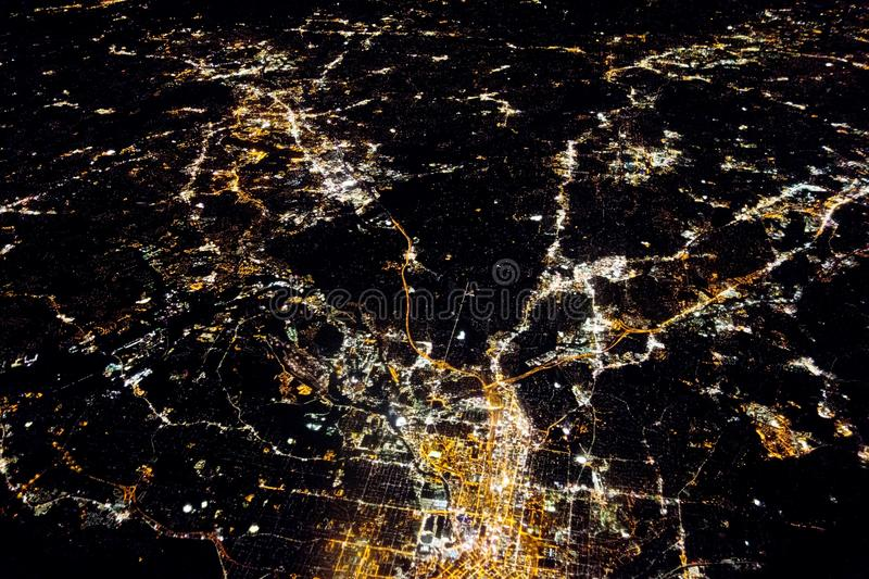 Flying at night over citiesbelow stock image