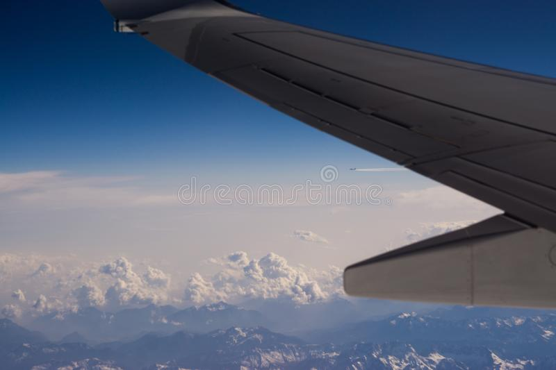 Flying over the Alps. An aerial view from the airplane over the mountains. Cloudscape and blue sky and atmosphere. Plane. Flying over the Alps. An aerial view royalty free stock photos
