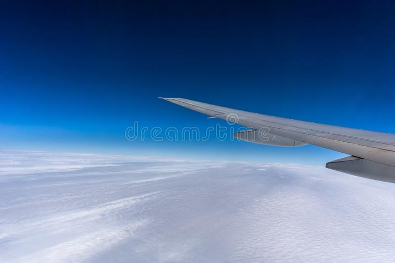 Flying over the clouds. Airplane wing. stock image