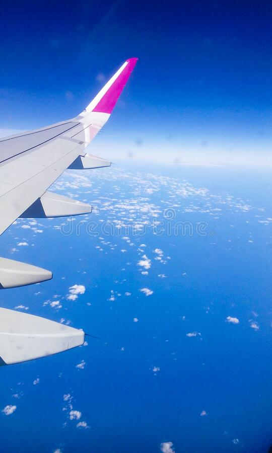 Flying over clouds in a clear day. With a airplane at high altitude stock image