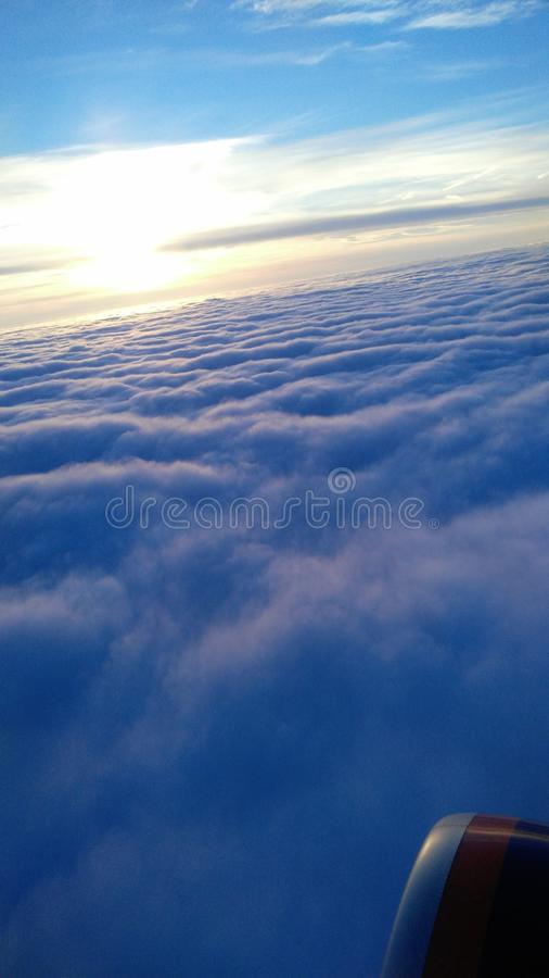 Flying over the clouds at sunset stock image