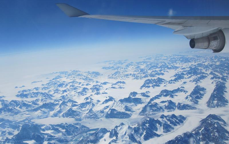 Flying over Greenland en route to Europe. Flying East over the snow and glaciers of Greenland on a long haul flight from the USA to Europe royalty free stock images