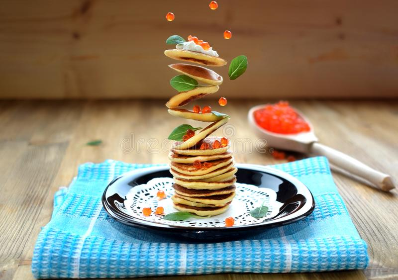 Flying pancakes, red caviar and basil leaves. Levitating food royalty free stock images