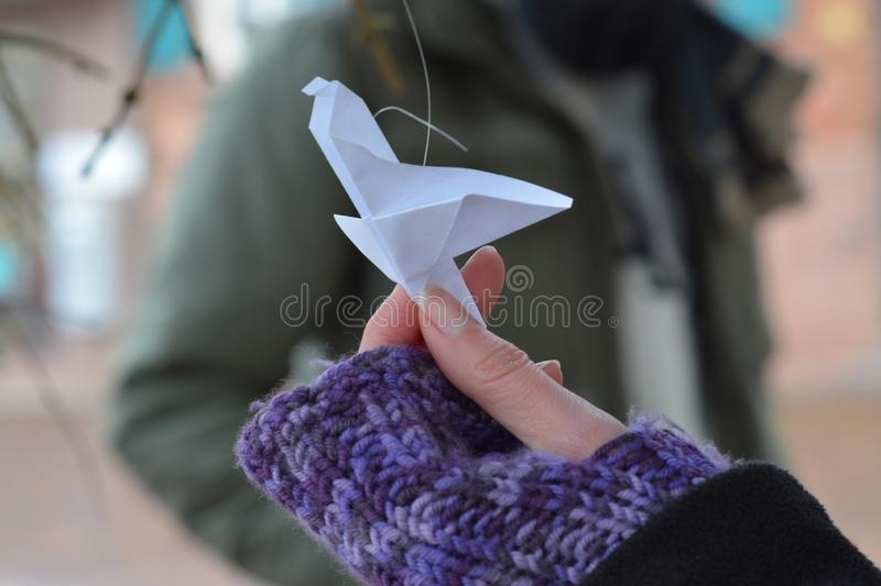 Flying paper bird origami held by a woman hand in winter closeup stock image