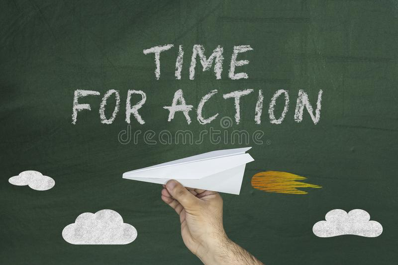 Flying paper plane and Time for action on green blackboard royalty free stock photography