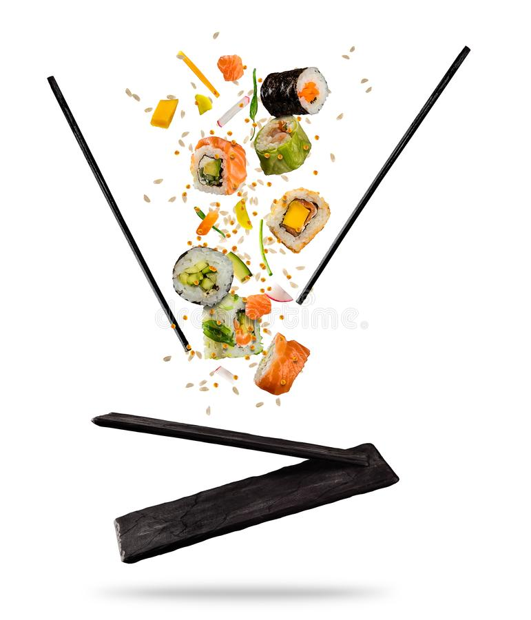 Flying pieces of sushi with wooden chopsticks and stone plate, i. Solated on white background. Flying food and motion concept. Very high resolution image stock photography
