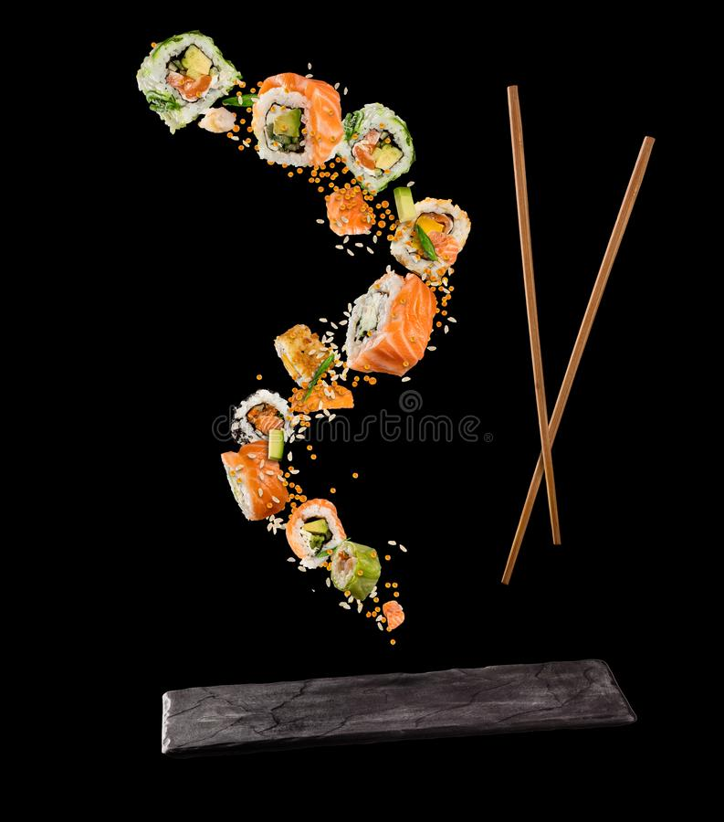 Flying pieces of sushi with wooden chopsticks and stone plate, i. Solated on black background. Flying food and motion concept. Very high resolution image stock images