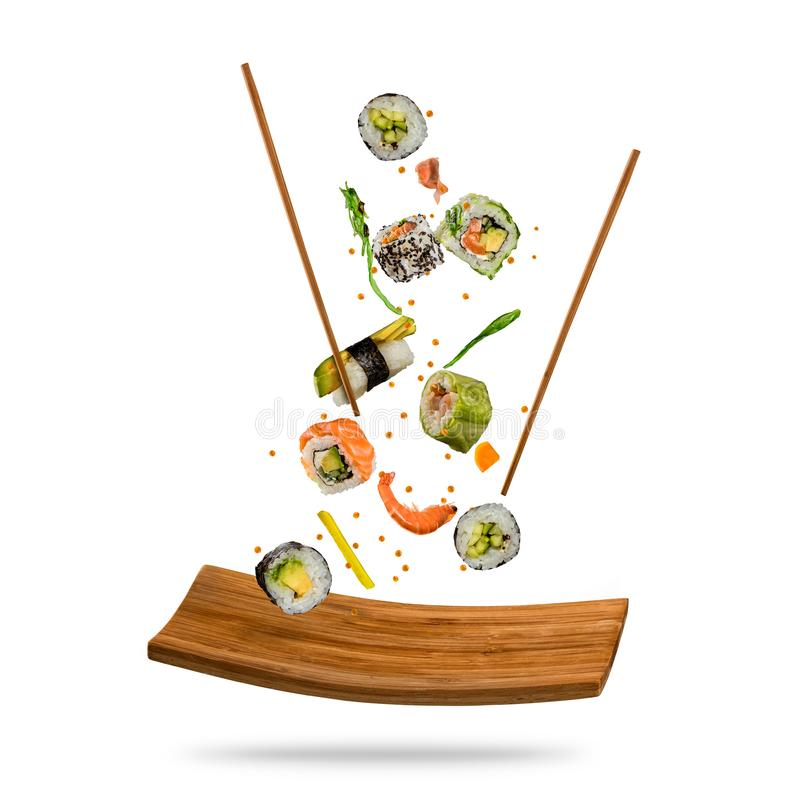 Flying pieces of sushi with wooden chopsticks and stone plate, i. Solated on white background. Flying food and motion concept. Very high resolution image stock image