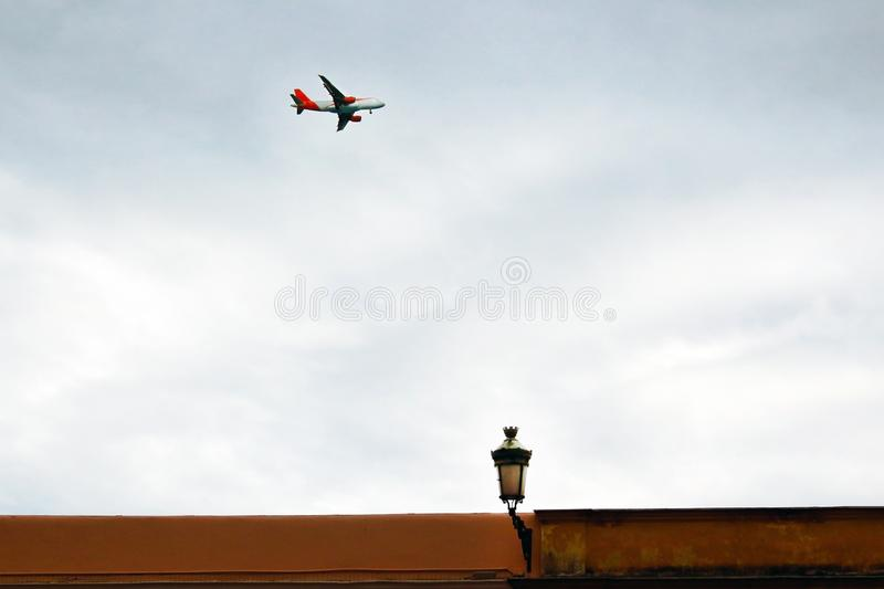 Flying plane on blue sky backgound with street light stock photography