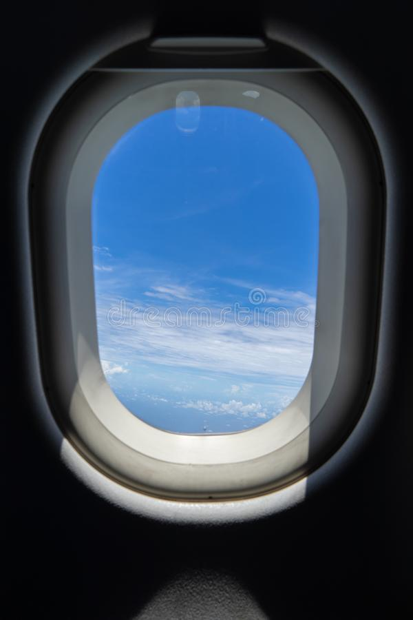 Flying on the plane seeing beautiful abstract white cloud and shades of bright blue sky background with afternoon sunlight. Through blurred window frame stock photo
