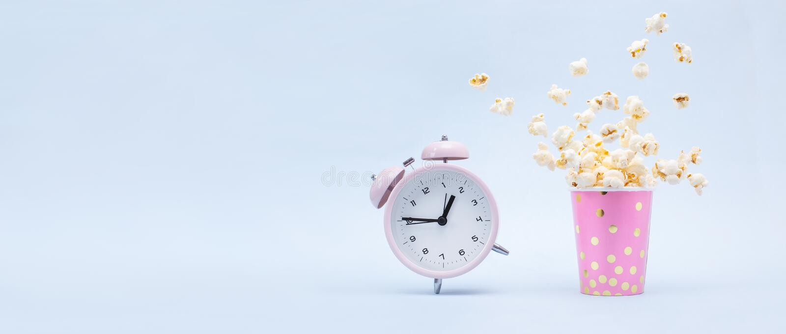 Flying Popcorn in a bright glass and a ringing alarm clock on a blue background. Time for a fun concept stock photos