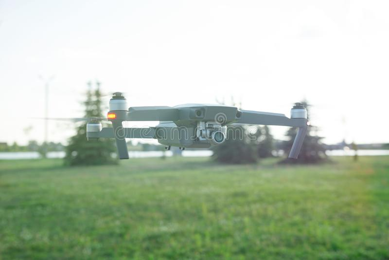 Flying quadcopter drone with Action Camera in the park under blue sky with lens flare. stock images