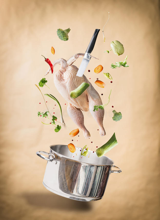 Flying raw chicken stock ,bouillon or soup ingredients with whole chicken, vegetables,seasoning, knife and cooking pot at natural stock photography