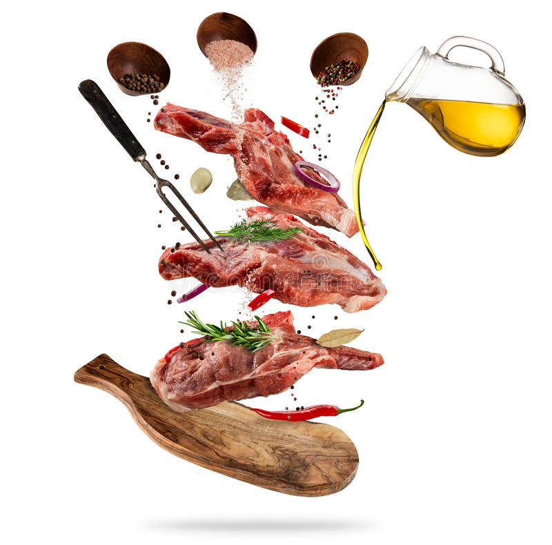 Flying raw pork steaks with ingredients, food preparation concept stock image