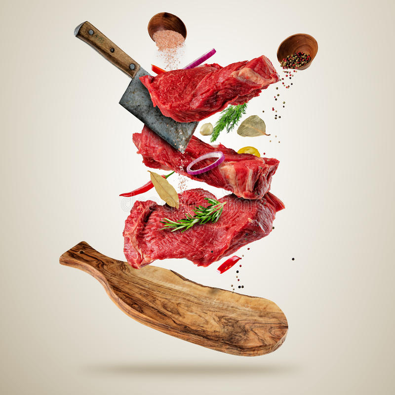 Flying raw steaks with ingredients, food preparation concept royalty free illustration