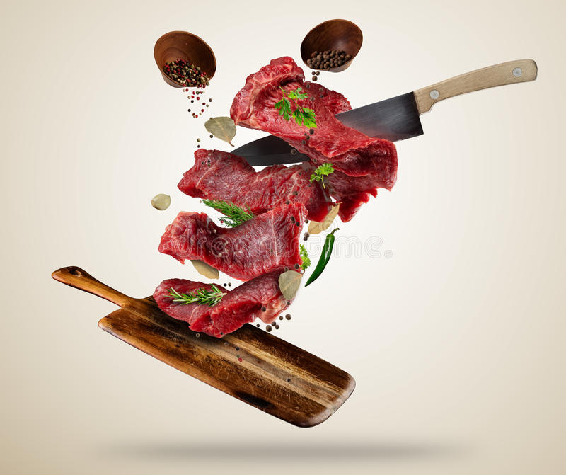 Flying raw steaks with ingredients, food preparation concept royalty free stock photos