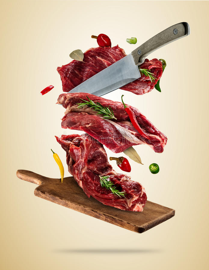 Flying raw steaks with ingredients, food preparation concept stock photos