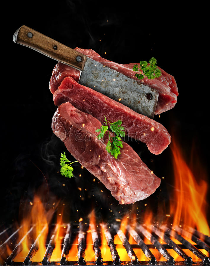 Flying raw steaks with meat cleaver, food preparation concept. Flying raw steaks with meat cleaver, barbecue grill with fire flames. Concept of food preparation stock images