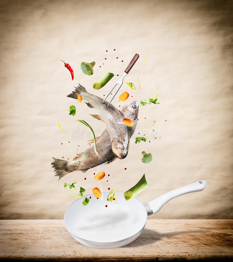Flying raw whole trout fishes with vegetables, oil and spices ingredients above frying pan for tasty cooking on desk kitchen table royalty free stock image