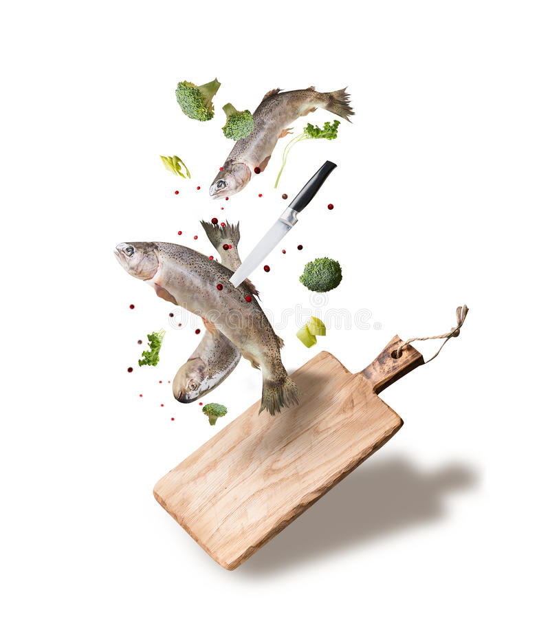 Flying raw whole trout fishes with vegetables, oil and spices ingredients above wooden cutting board for tasty cooking, isolated o stock photography