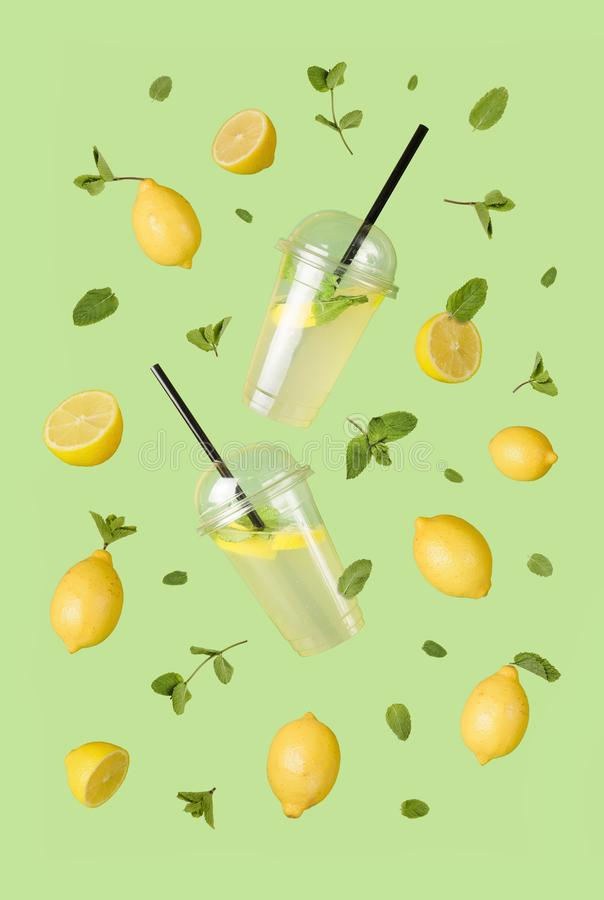 Flying refreshing lemonade from a plastic cups with flying lemons & mint leaves on a green background. Jar full of cold cocktail. royalty free stock photography