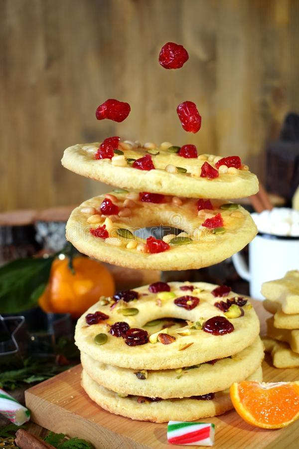 Flying shortbread cookies shaped as rings decorated with dried cherries and nuts royalty free stock photography