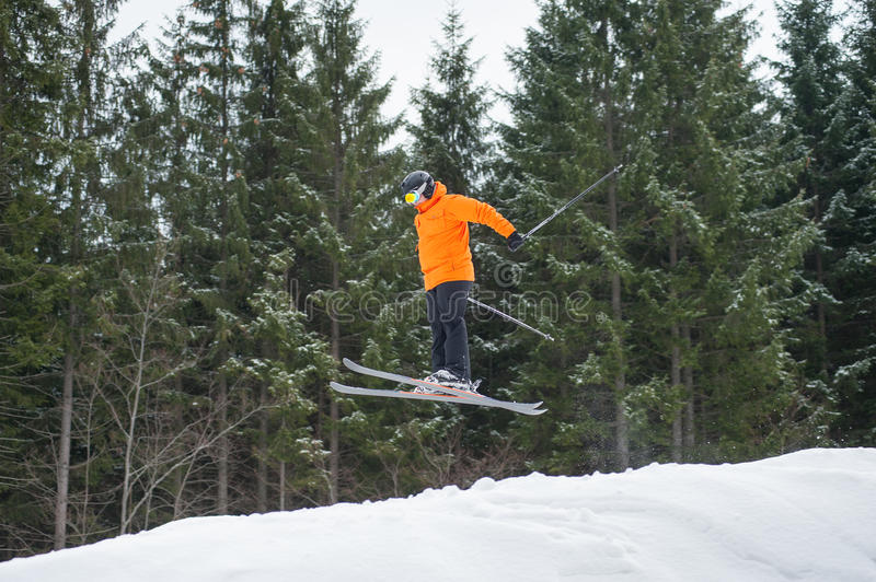 Flying skier man at jump from the slope of mountains. In orange jacket performing a high jump and looking apprehensive about the landing with forest in stock photography