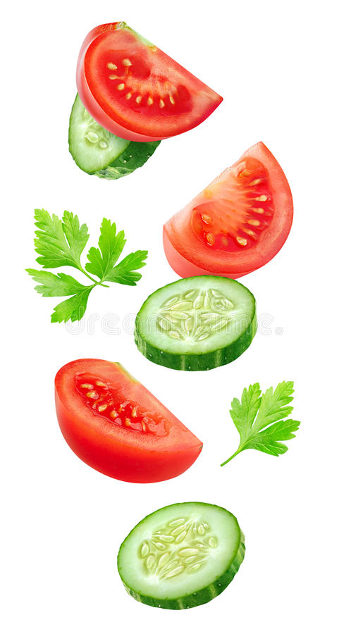 Flying slices of tomato and cucumber royalty free stock image
