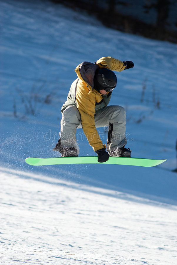 Flying Snowboard man. On green board stock photo