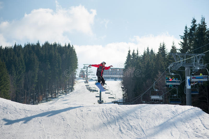 Flying snowboarder at jump from the slope of mountain. S in orange jacket performing a high jump, with forest and ski lifts in background royalty free stock photography