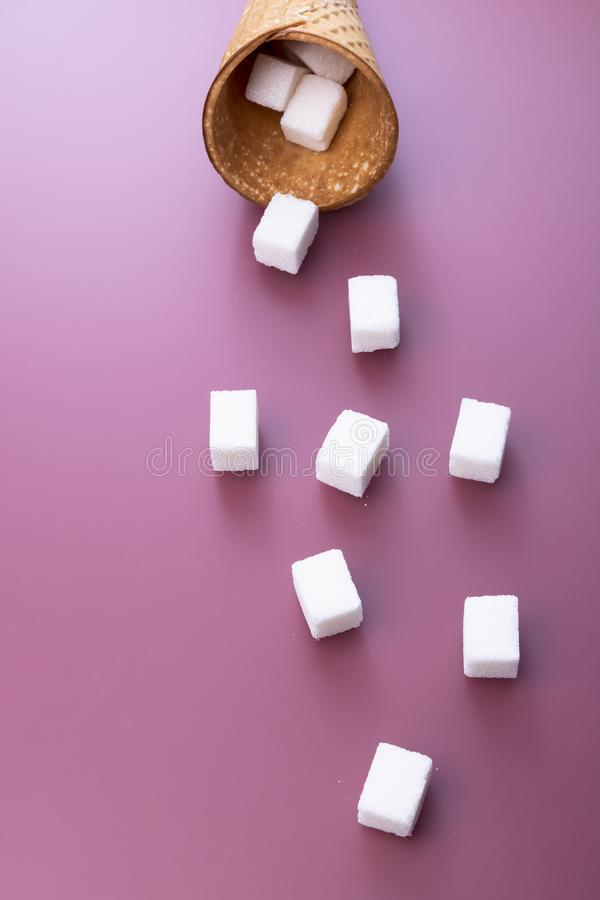 Flying sugar. Flying sugar cubes from ice cream cone on red background. Copy space for text. Top view. Vertical stock images