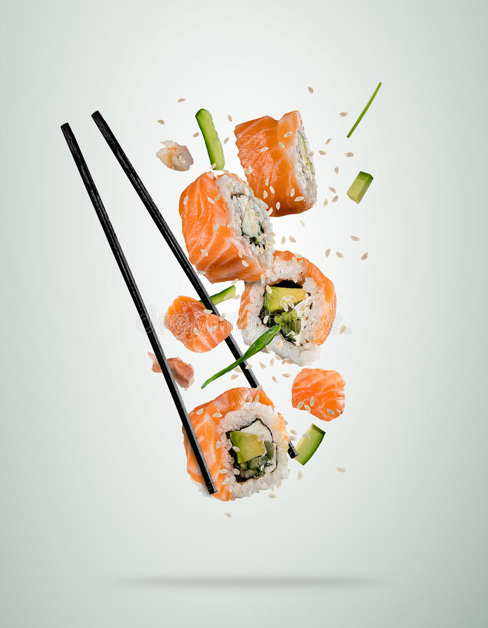 Flying sushi pieces with chopsticks, separated on soft background royalty free stock photography