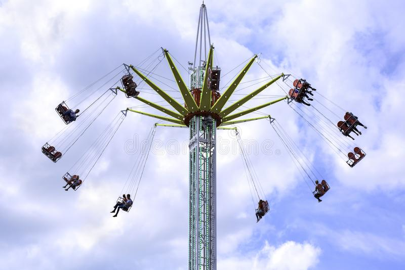 People enjoy a ride on a flying swing ride at an amusement park stock photos