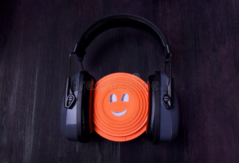 Flying target plate with cute face in noise suppression headphones stock images